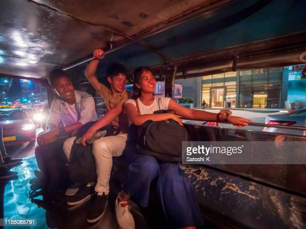 multi-ethnic asian friends riding jeepney in manila at night - jeepney stock pictures, royalty-free photos & images