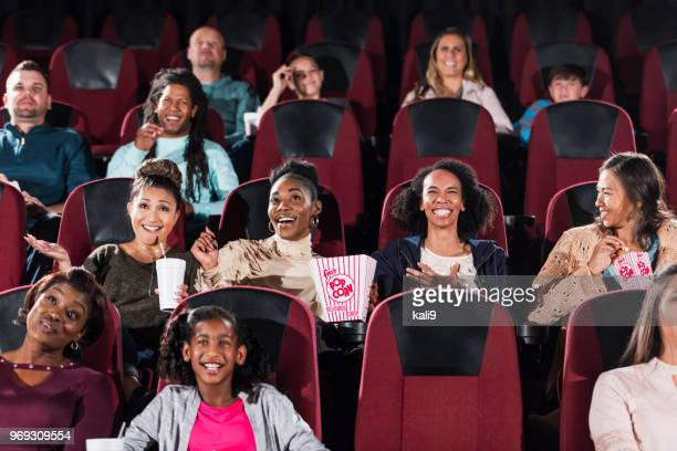 Multi-ethnic audience watching movie in theater