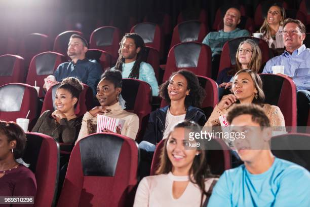 multi-ethnic audience watching movie in theater - girlfriends films stock pictures, royalty-free photos & images