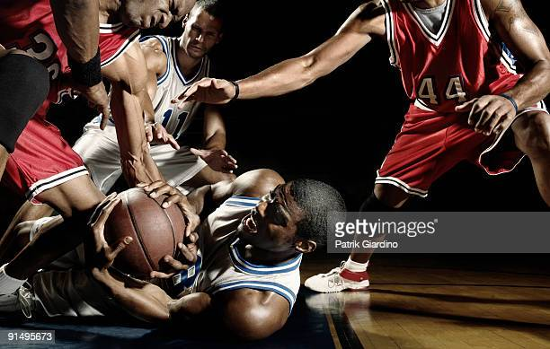 multi-ethnic basketball players struggling for basketball - basketball team stock pictures, royalty-free photos & images