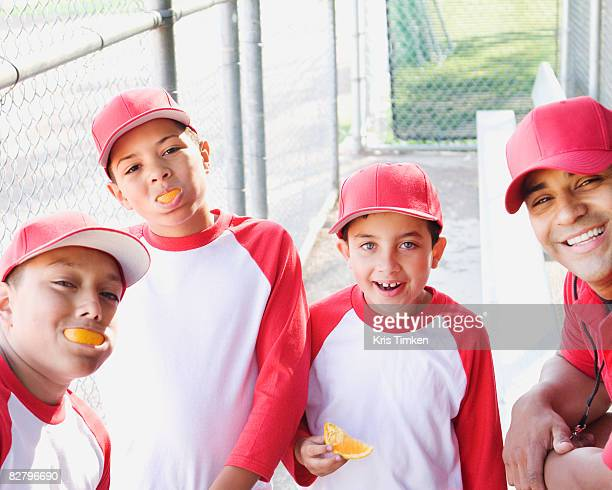 Multi-ethnic boys in baseball uniforms and coach in dugout eating oranges
