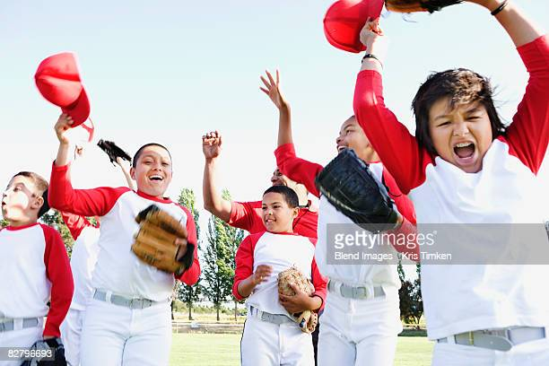 Multi-ethnic boys in baseball uniforms celebrating