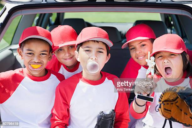multi-ethnic boys in baseball uniforms making faces and holding trophy - baseball strip stock pictures, royalty-free photos & images