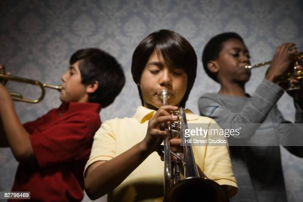 Multi-ethnic boys playing trumpets