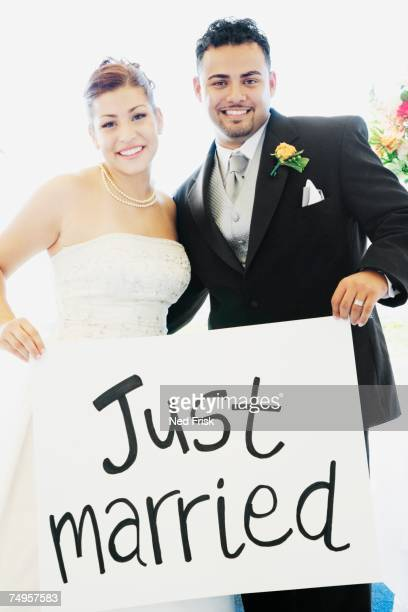 Multi-ethnic bride and groom holding sign