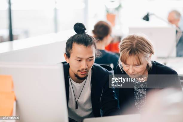Multi-ethnic business colleagues using laptop at office