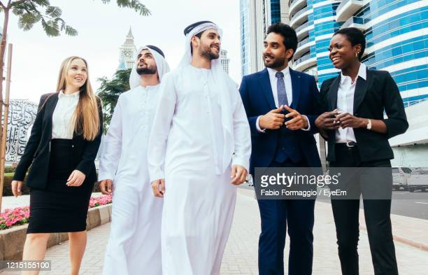 multi-ethnic business colleagues walking against office - abu dhabi stock pictures, royalty-free photos & images