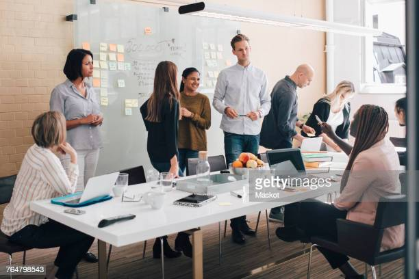 multi-ethnic business coworkers discussing during meeting in board room at office - werkstatt stock-fotos und bilder