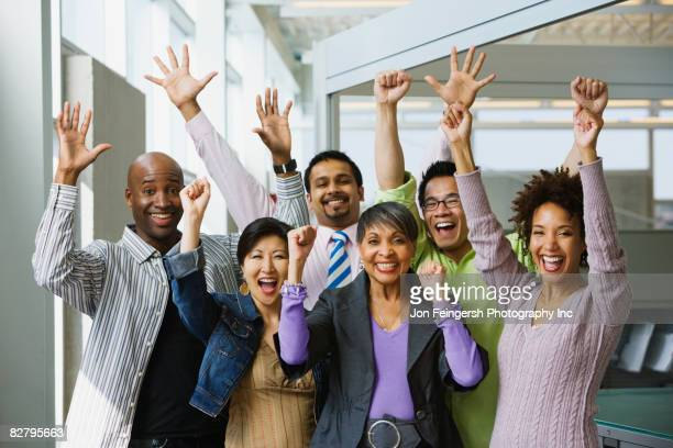 Multi-ethnic business people celebrating in office