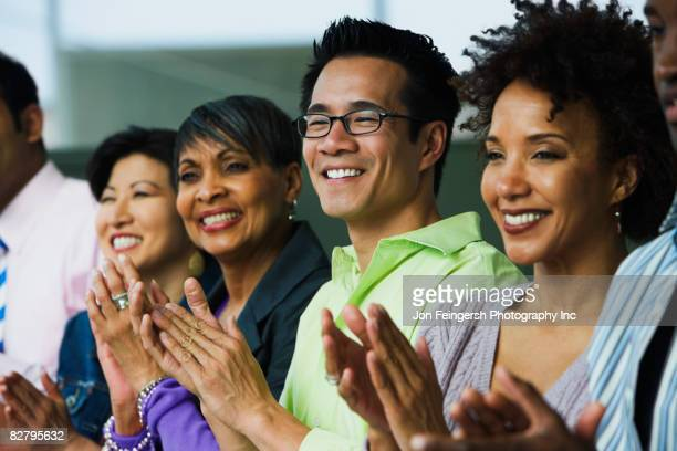 Multi-ethnic business people clapping
