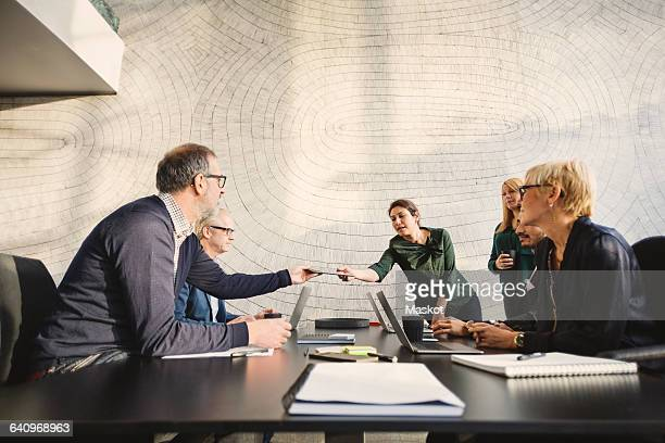 Multi-ethnic business people discussing at table in creative office