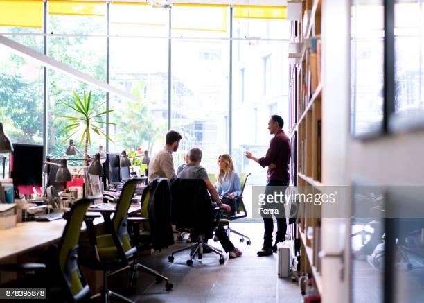 multi-etnische zakenmensen bespreken in kantoor - informeel zakelijk stockfoto's en -beelden