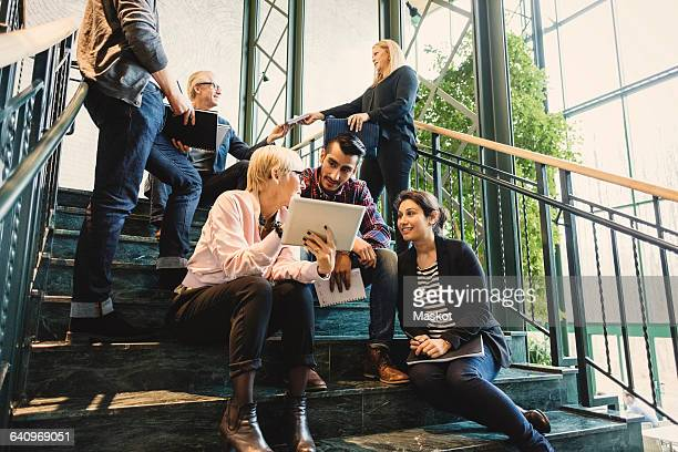 Multi-ethnic business people discussing on stairway in creative office