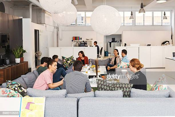 Multi-ethnic business people discussing project in modern office lobby