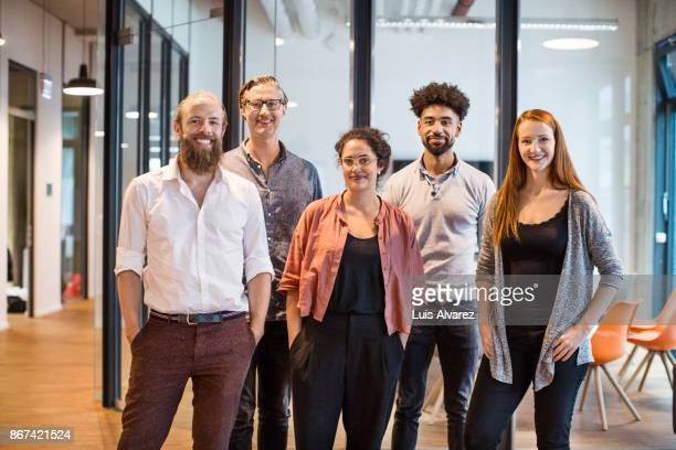 multi-ethnic business people smiling in creative office - five people stock pictures, royalty-free photos & images