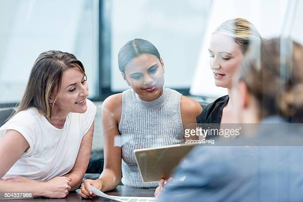 Multiethnic business people using tablet in meeting
