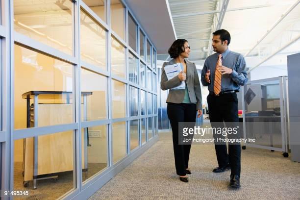 Multi-ethnic business people walking down office corridor