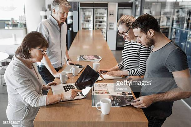 Multi-ethnic business people working at counter in office cafe