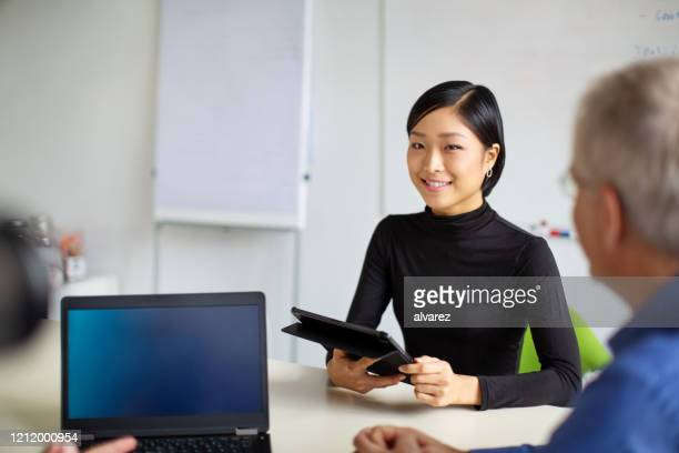 multi-ethnic business team having a meeting in office - three people stock pictures, royalty-free photos & images