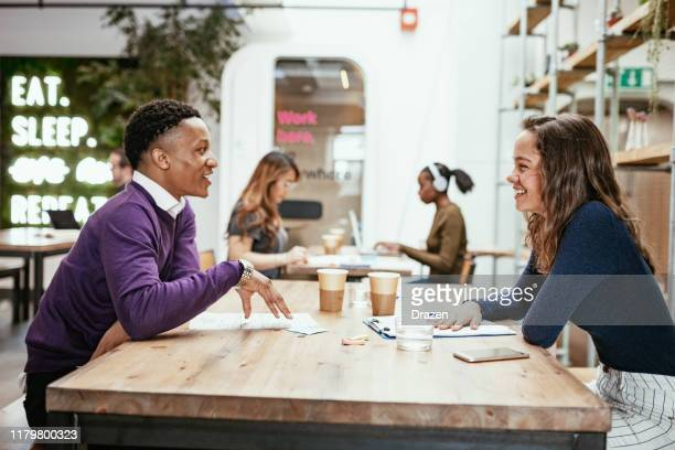 multi-ethnic business team in coworking space discussing investments - place of work stock pictures, royalty-free photos & images