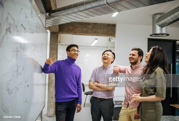 multi-ethnic business team laughing near whiteboard - eastern european descent stock pictures, royalty-free photos & images