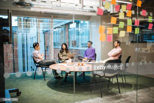multi-ethnic business team sitting at round table in modern office in london - responsible business stock photos and pictures