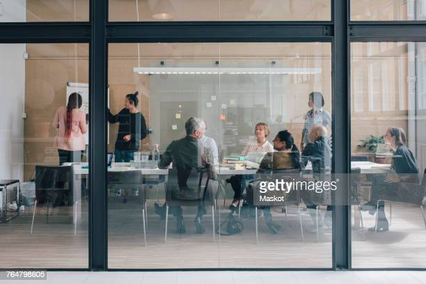 multi-ethnic business team sitting in board room at office seen from glass - vidro - fotografias e filmes do acervo