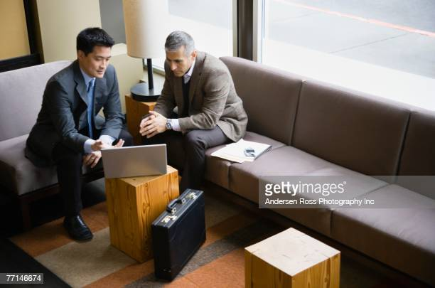 Multi-ethnic businessmen looking at laptop