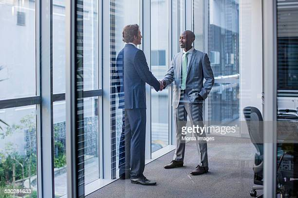 multi-ethnic businessmen shaking hands in office - full suit stock pictures, royalty-free photos & images