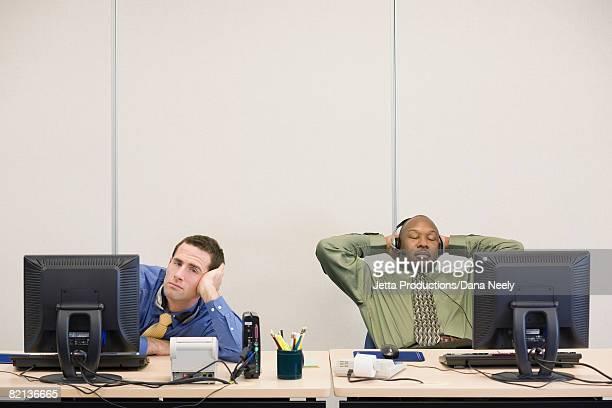 multi-ethnic businessmen sitting at desks - 遅い ストックフォトと画像