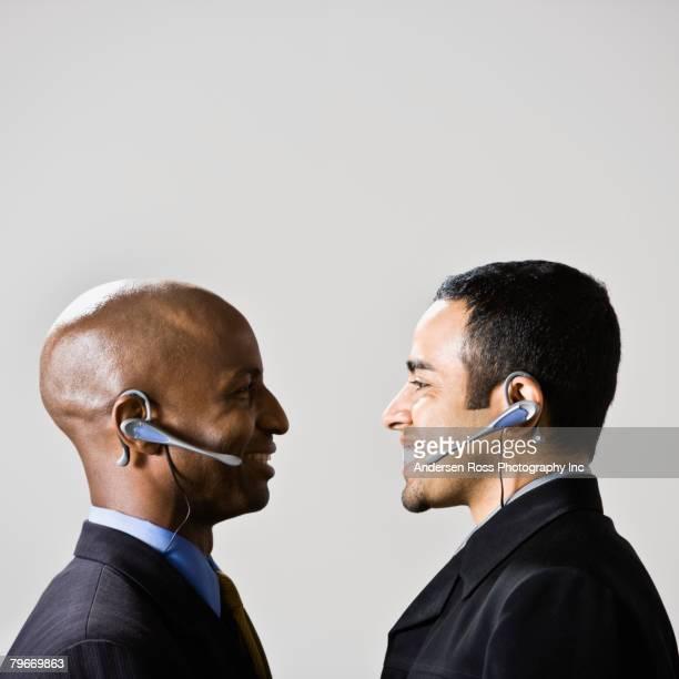 Multi-ethnic businessmen wearing headsets