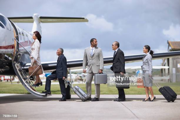 Multi-ethnic businesspeople getting on airplane