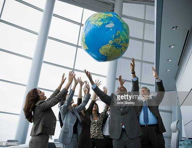 multi-ethnic businesspeople playing with globe ball - international match photos et images de collection