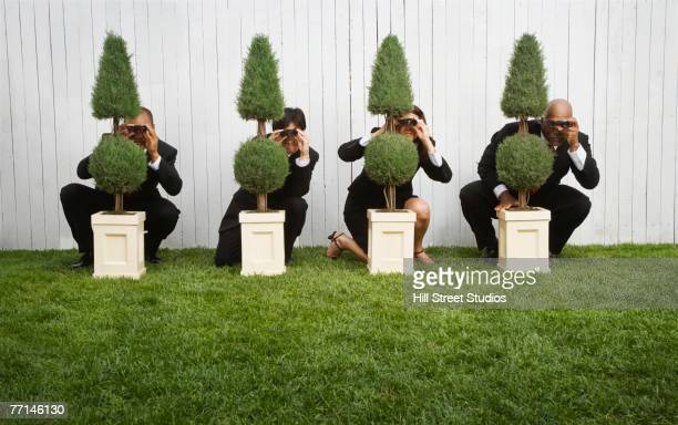 Multi-ethnic businesspeople spying from behind bushes