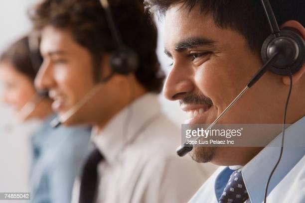 Multi-ethnic businesspeople wearing headsets