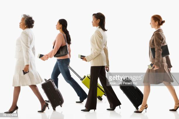 Multi-ethnic businesswomen pulling suitcases