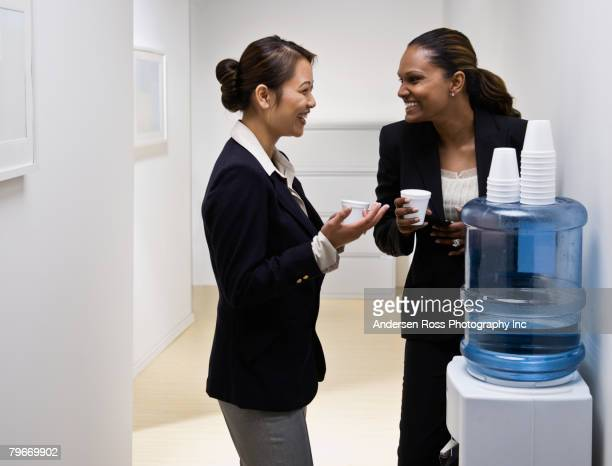 multi-ethnic businesswomen talking at water cooler - water cooler stock photos and pictures