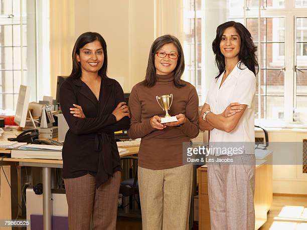 Multi-ethnic businesswomen with trophy