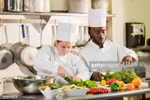 multi-ethnic chefs chopping vegetables - farm to table stock photos and pictures