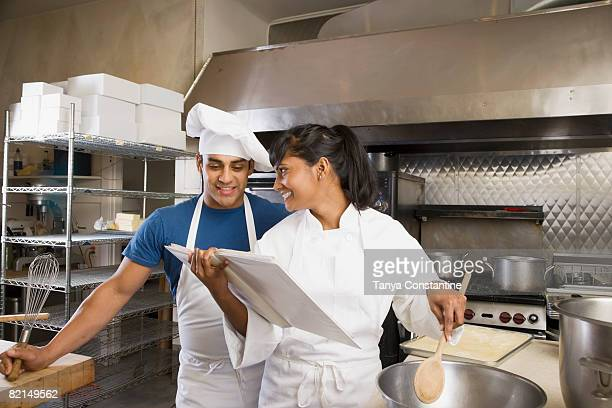 Multi-ethnic chefs looking at cookbook