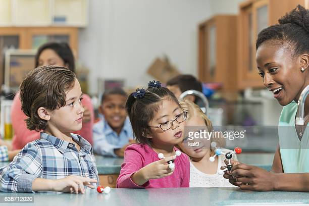 Multi-ethnic children and teacher in science class