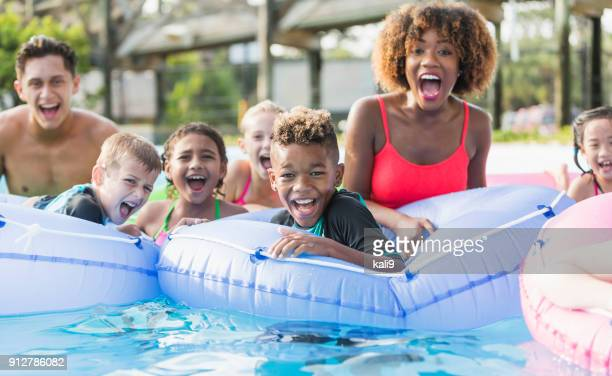 multi-ethnic children and young adults at water park - pool party stock pictures, royalty-free photos & images