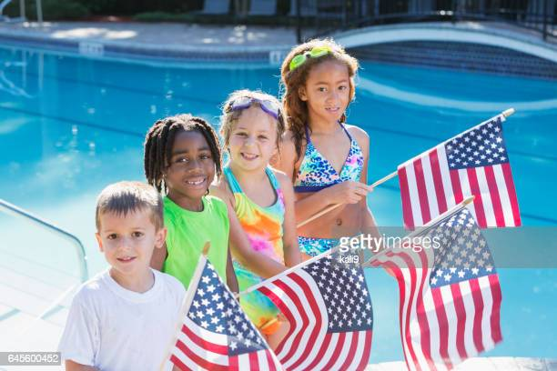 Multi-ethnic children at pool holding American flags