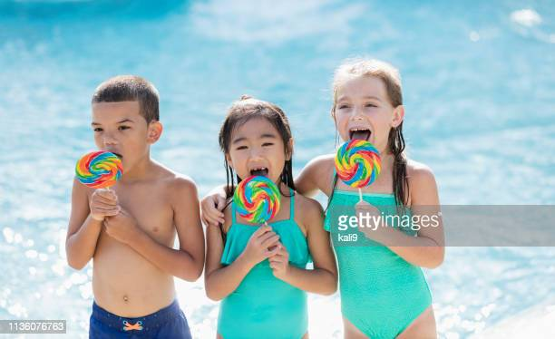 Multi-ethnic children at swimming pool with lollipops