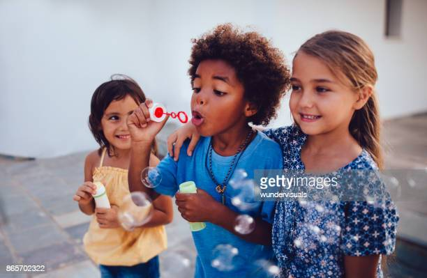 multi-ethnic children best friends blowing bubbles on summer holidays - mixed race person stock pictures, royalty-free photos & images