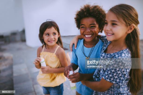 Multi-ethnic children best friends having fun with bubbles in summer