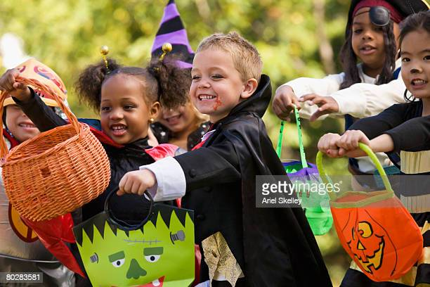 multi-ethnic children dressed in halloween costumes - halloween party stock photos and pictures