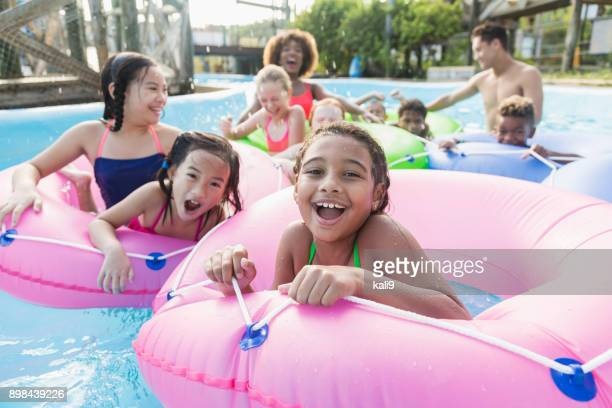 multi-ethnic children, fun on lazy river at water park - minority groups stock pictures, royalty-free photos & images