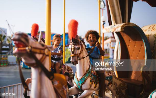 multi-ethnic children having fun on funfair merry-go-round carousel ride - carnival stock photos and pictures