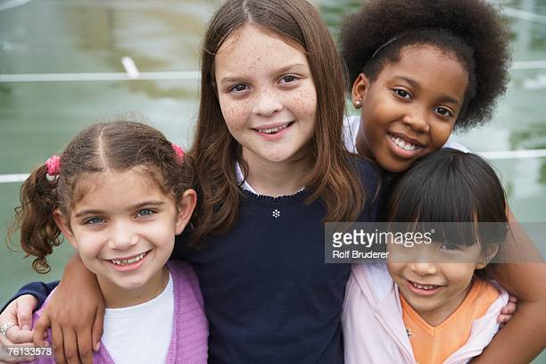 multi-ethnic children hugging - only girls stock pictures, royalty-free photos & images